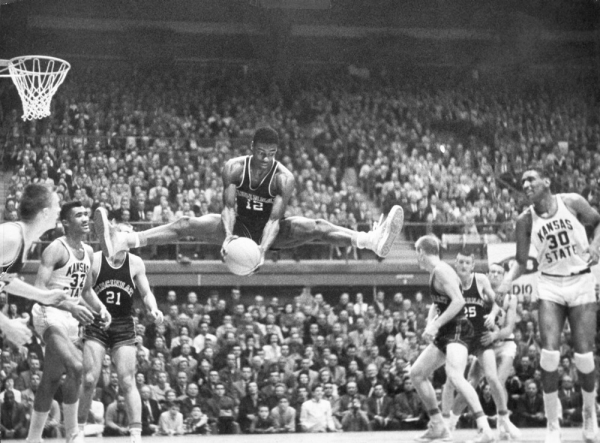 Oscar Robertson rebounds the ball and is suspended in midair with both legs nearly straight out like the splits.