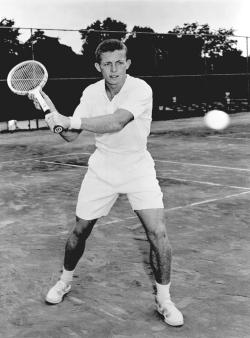 Former UC tennis great Tony Trabert swings his racket at a tennis ball.