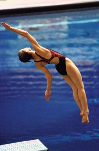 Becky Ruehl begin to flip mid-dive in an image that shows the board and blue water beneath.