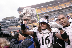 UC football players hold up the newspaper headline that reads 'Big East Champs!'