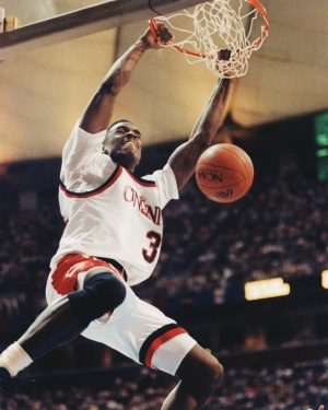 Herb Jones hangs from the rim after dunking the basketball.