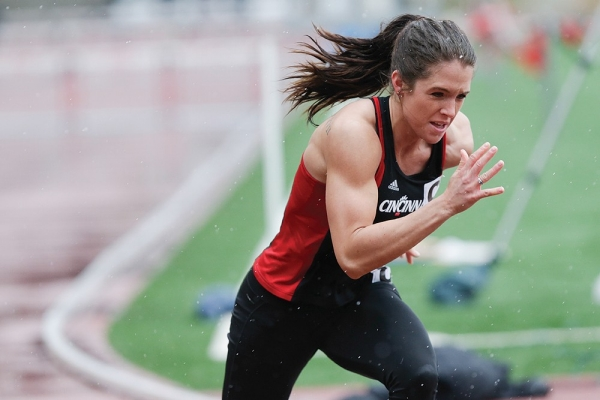 A female runner from the University of Cincinnati track team competes in the rain.