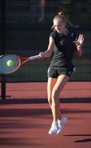 A female UC tennis player leaves her feet as she returns a ball at the Trabert-Talbert Tennis Center.