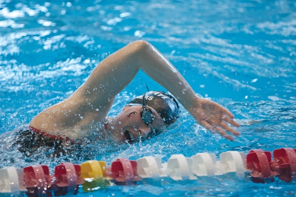 A photo captures a UC swimmer in the middle of an overhand swim stroke in a closeup image as she turns to take a breath inside the Keating Aquatics Center.