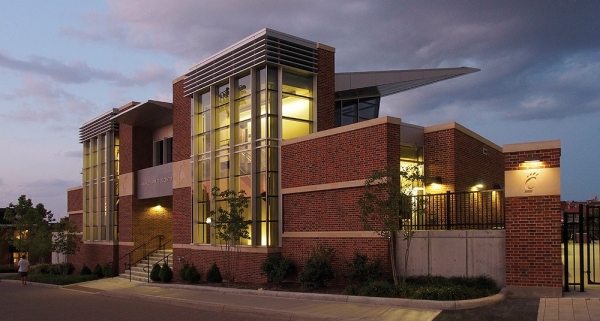 Indoor lights illuminate the new Sheakley Athletics Center, a mostly brick and glass structure, at dusk.