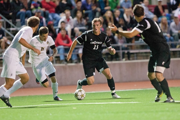 No. 23, a male Bearcat soccer player in a black uniform, dribbles the soccer ball around two defenders.