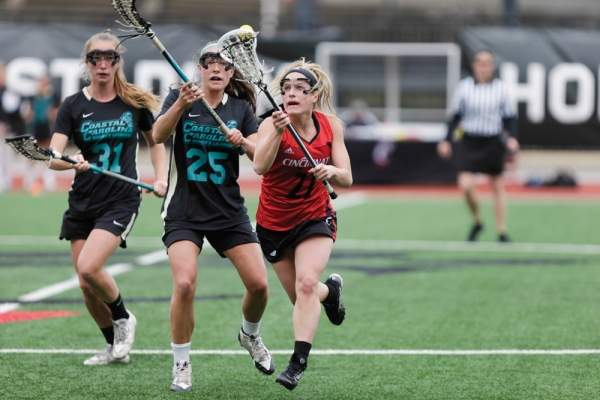A UC lacrosse player outruns two competitors while keeping the ball in the webbing of her stick.