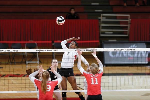 A A female UC volleyball player prepares to spike the ball over the net inside Fifth Third Arena.