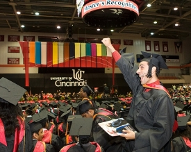 "With his first copy of ""UC Magazine"" in hand, a new UC alumnus shouts for joy after receiving his doctoral hood.  photo/Lisa Ventre"