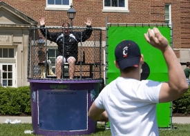 A student takes aim at UC head football coach Brian Kelly during Grad Bash on McMicken Commons.