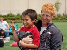 Former UC runner and scholar athlete Patrick Starkey, CAHS '08, bonds with one of the youngsters who came to campus as part of a Special Olympics event.