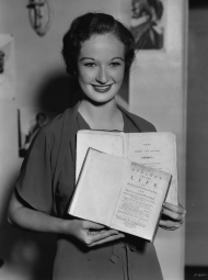 Early in her movie career, Venable holds two books.