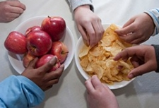 hands reaching for apples and potato chips