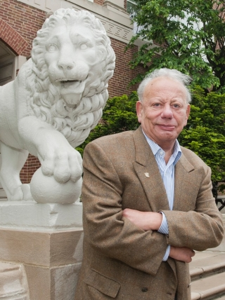 Sigmund Rolat on campus in front of one of the stone lions.