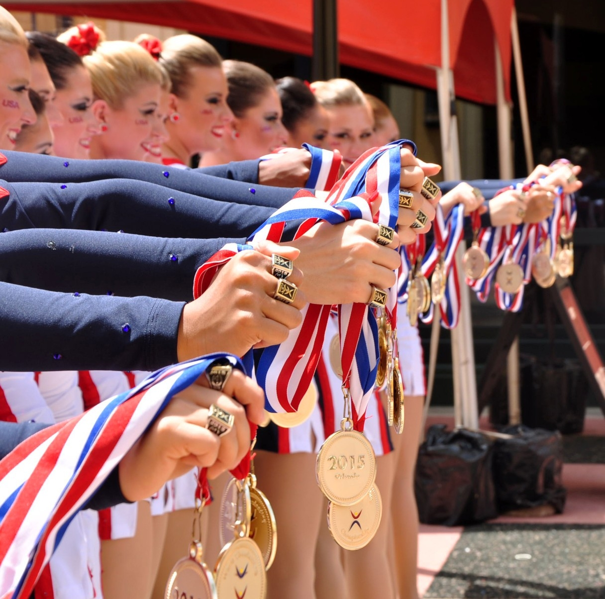 A long line of women holding gold medals out in front of themselves. The UC Dance Team represented the U.S. in an international competition and won.