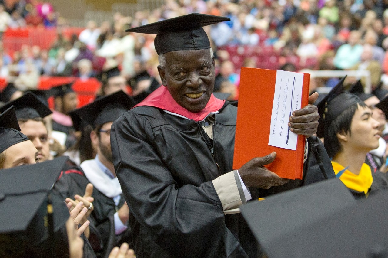 A smiling 82-year-old graduate holds up his copy of his thesis during the University of Cincinnati commencement ceremony.