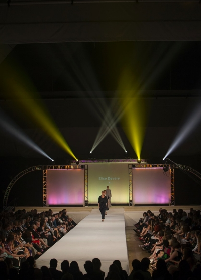 Colorful lights beam up a dark background behind the runway during the UC DAAP fashion show.