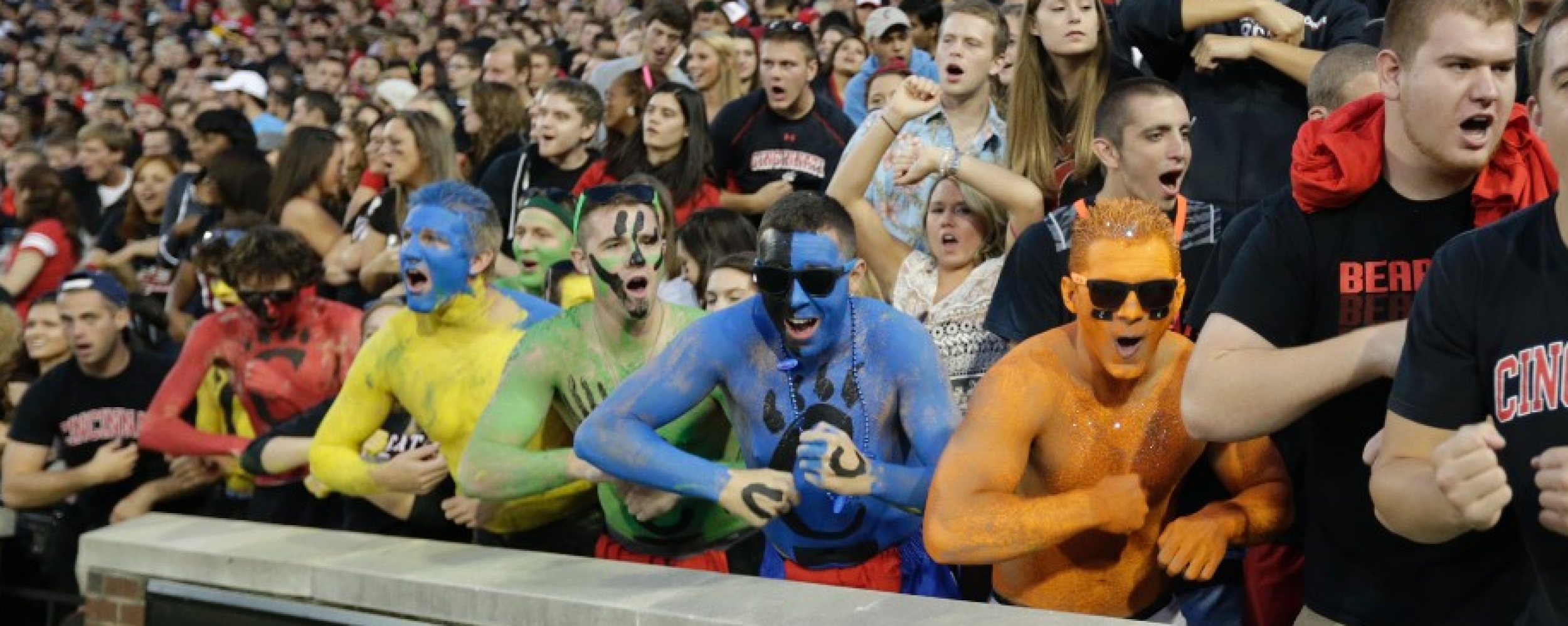 University of Cincinnati students, with faces painted bright colors, roll their hands as part of a cheer.