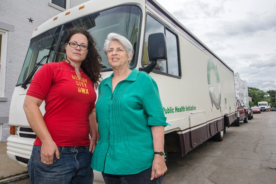 Libby Harrison and Dr. Judith Feinberg stand in front of the mobile needle exchange RV.