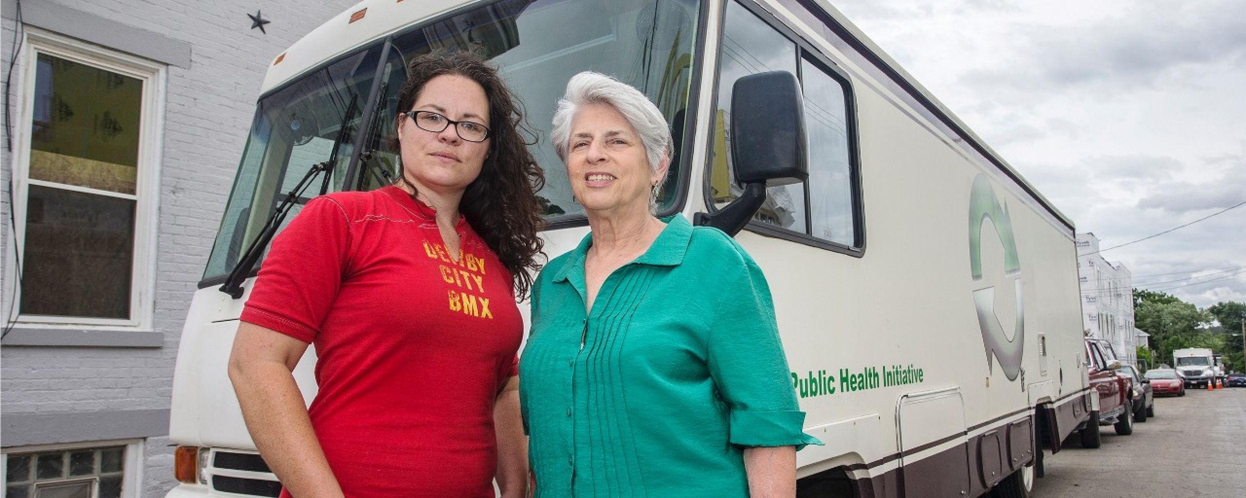 Dr Judith Feinberg and Libby Harrison stand in front of the Cincinnati Needle Exchange RV.