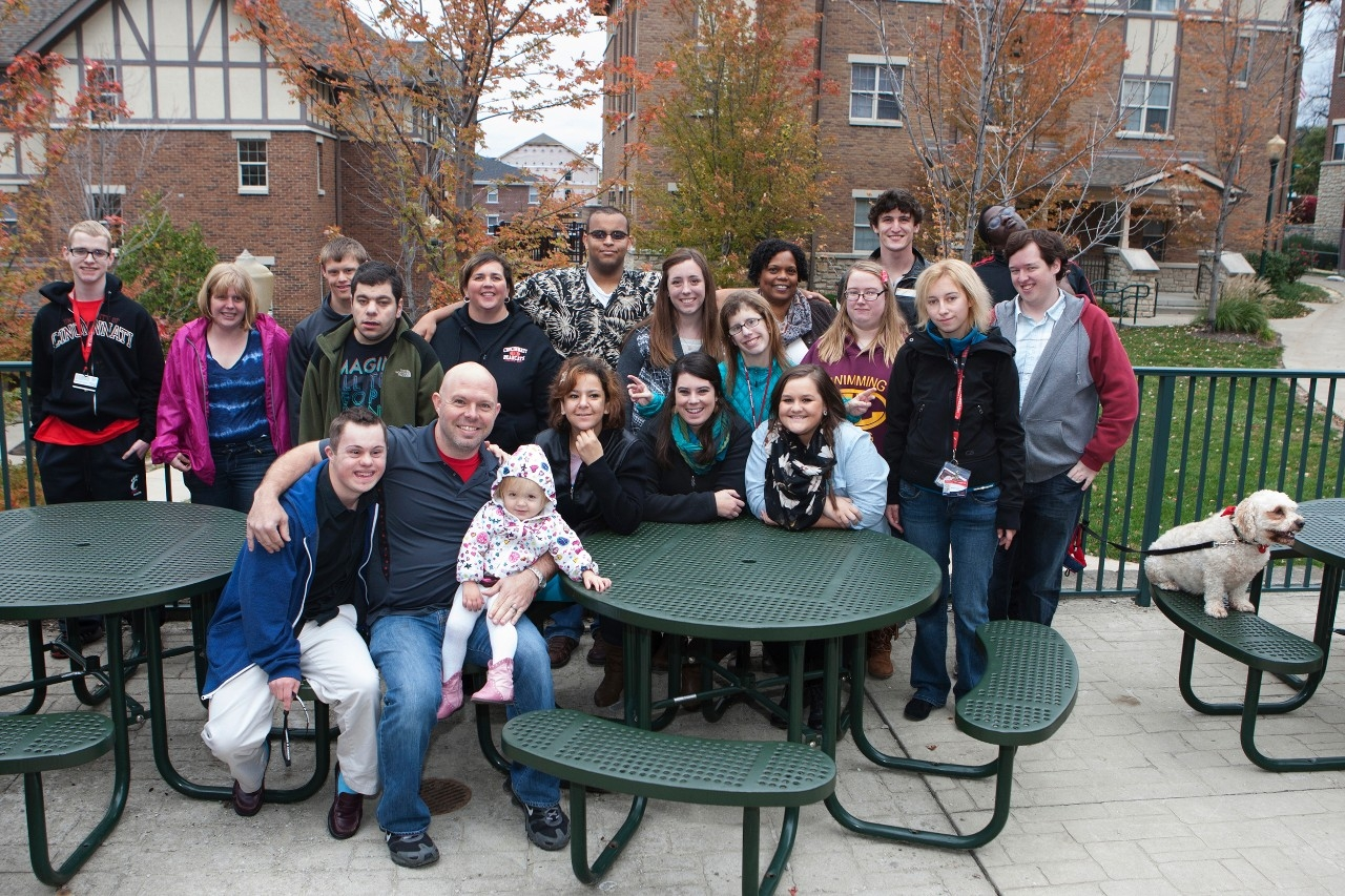 A large group of students, staff and family from UC's TAP program pause during a picnic for a photo.