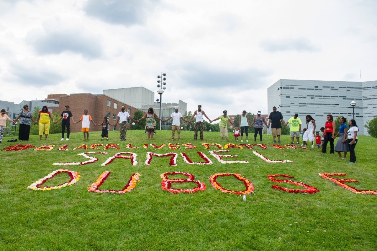 Family and friends of Samuel DuBose hold hands around a rose memorial as part of a remembrance on campus Aug. 9, 2015.