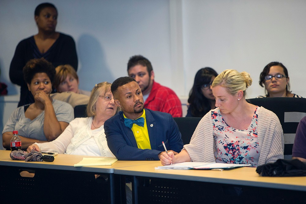 UC community sits at a table and listens during a discussion about Samuel DuBose
