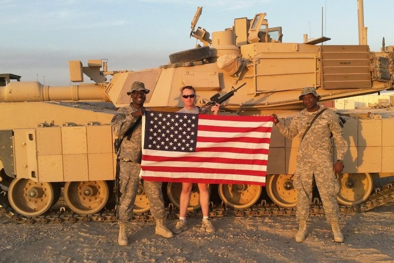 Terence Harrison and other soldiers pose in front of a tank in Iraq.