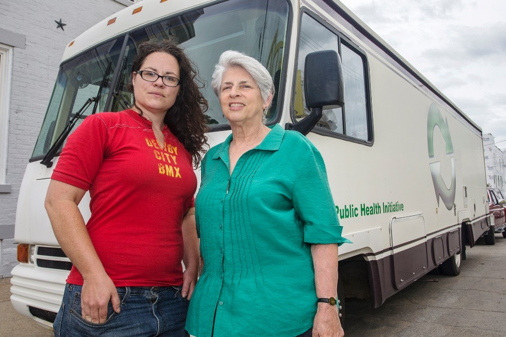 Two women stand before a van they use for a life-saving needle exchange program.