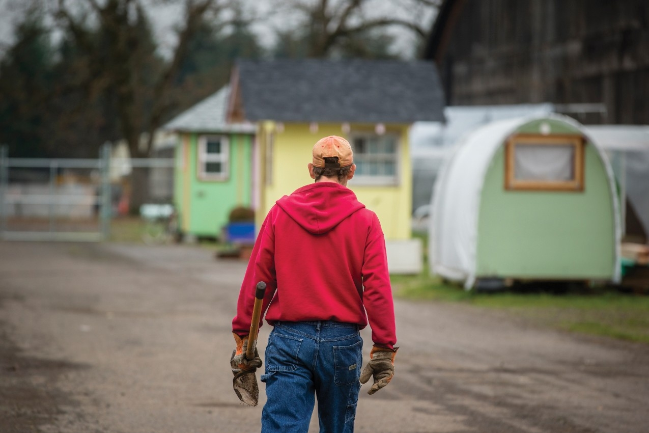 A man holding a shovel walks away from camera in Opportunity Village in Eugene, Oregon.