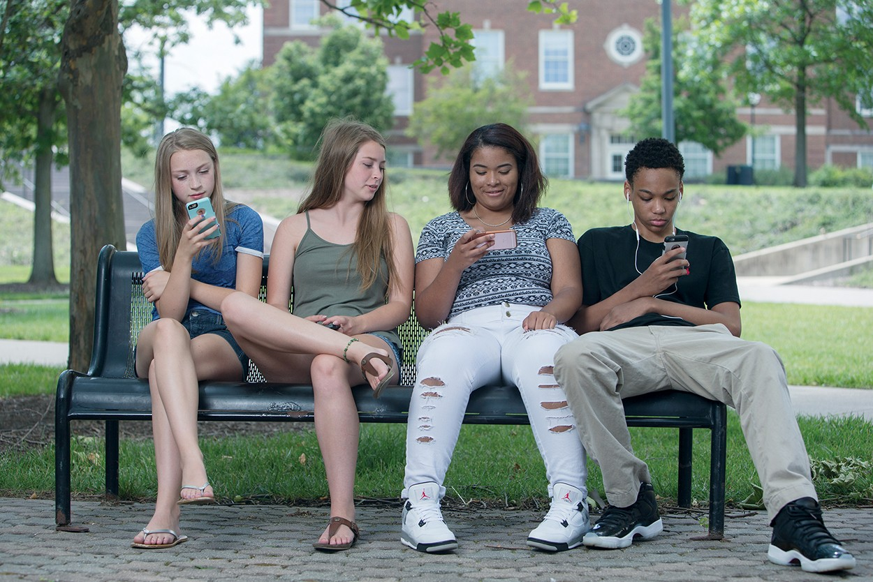 Future UC students sit on a bench on campus
