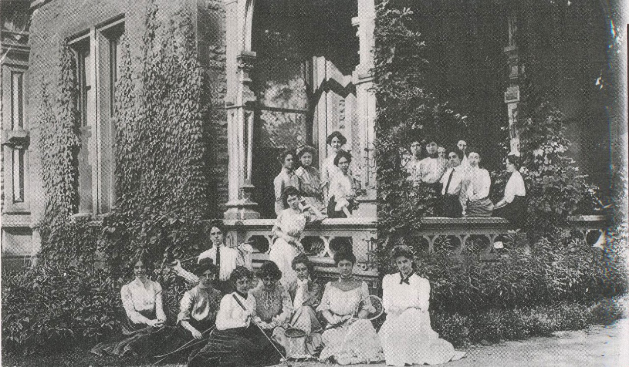 Students sit and stand outside a home in early 1900s
