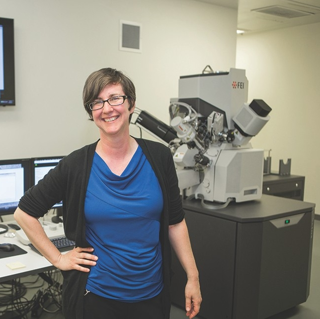 Melodie Fickenscherstands next to the dual-beam microscope