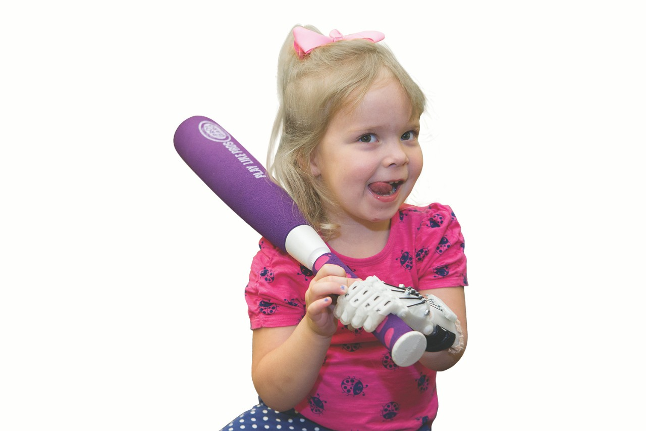 Ella Morton holds toy bat with prosthetic hand