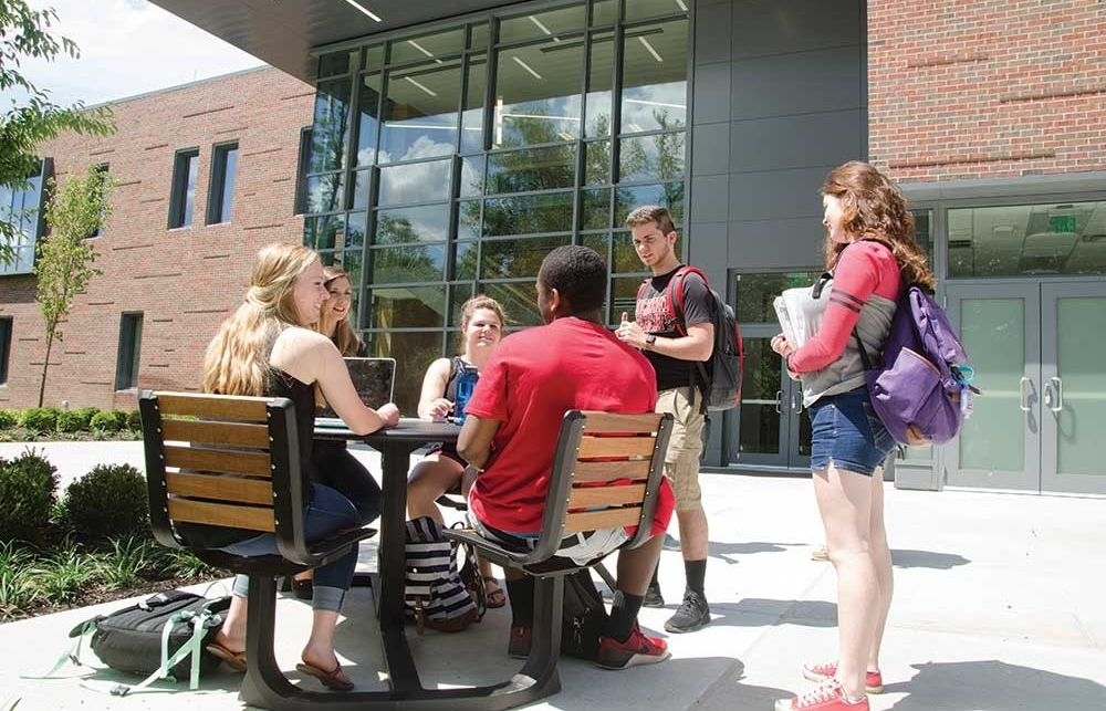 Students gather around a table outside at UC Blue Ash College