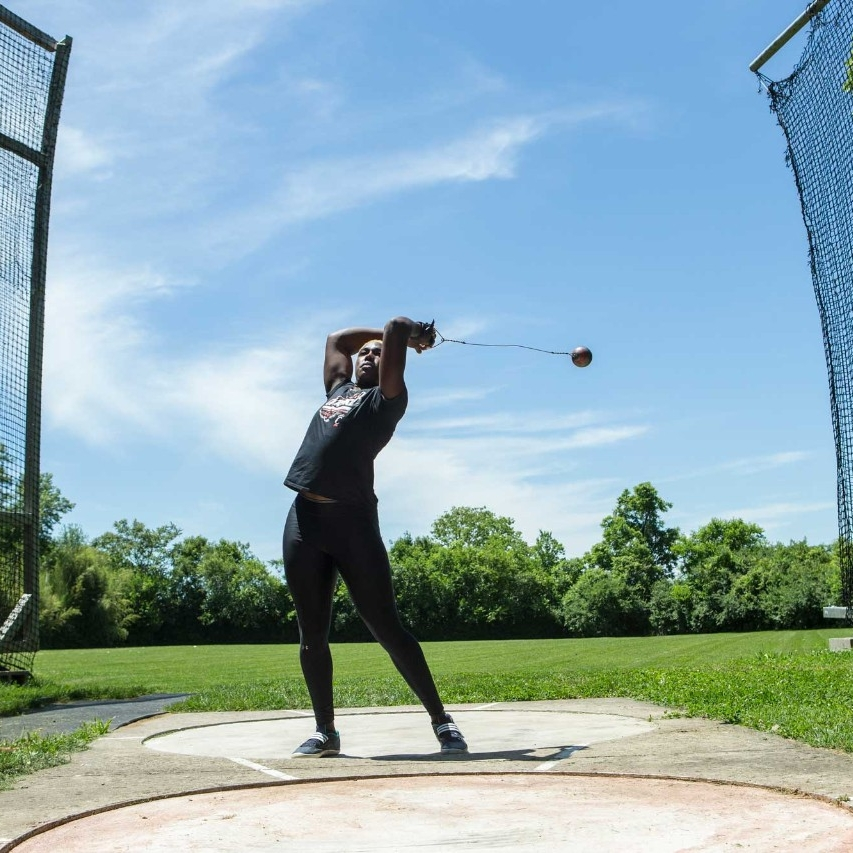 Echikunwoke demonstrates a hammer throw outdoors at Coy Field near UC's campus (1 of 3)