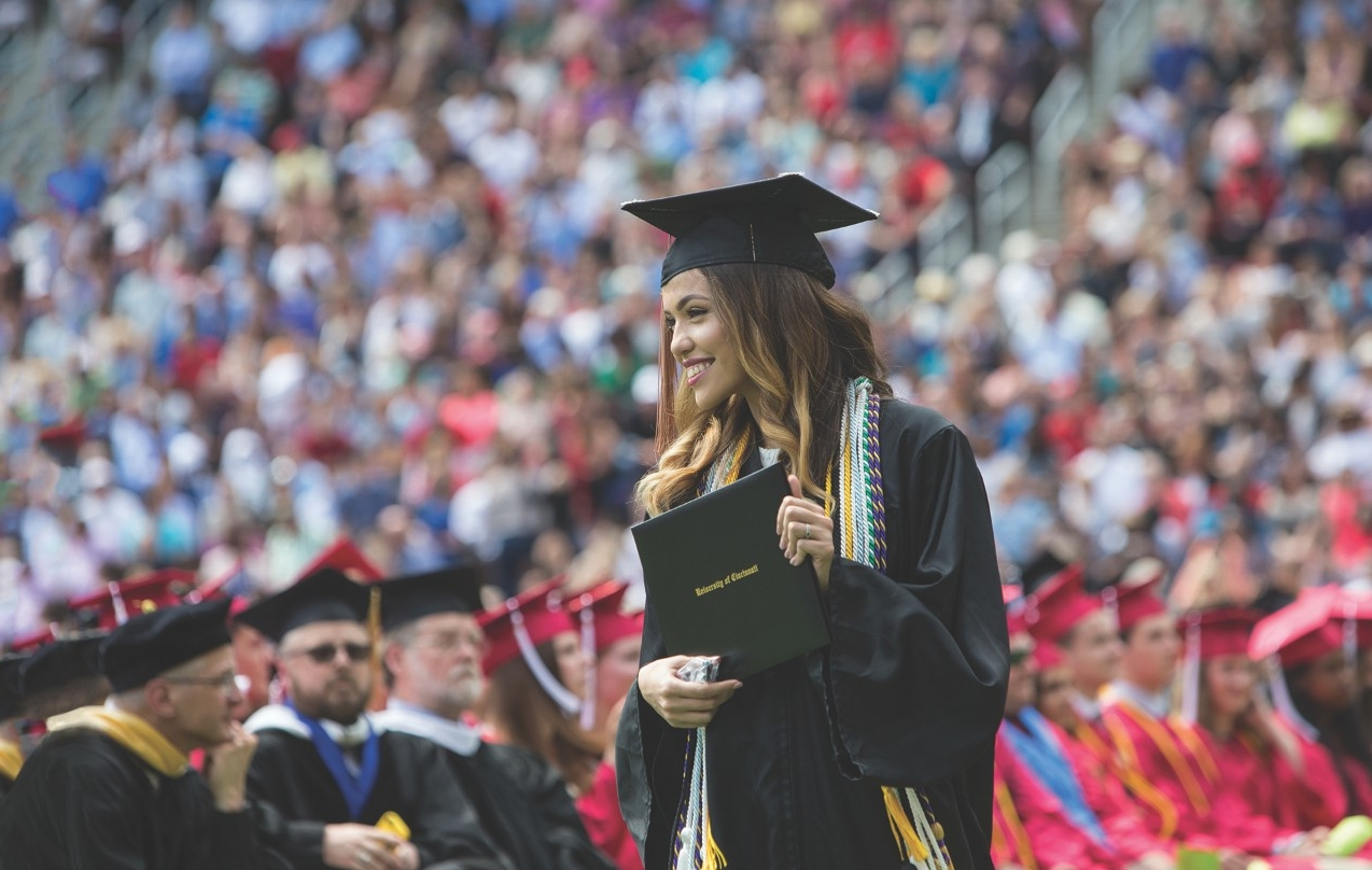 New graduate Codee Boyce holds her diploma after graduating inside Nippert Stadium in May 2017