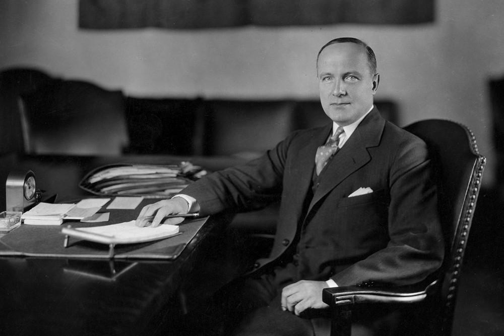 University of Cincinnati's longest serving president, Raymond Walters, a distinguished looking gentleman, sits at his desk.