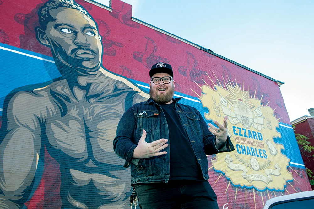 A University of Cincinnati alumnus and artist, Jason Snell, stands in front of his large mural of boxer Ezzard Charles.
