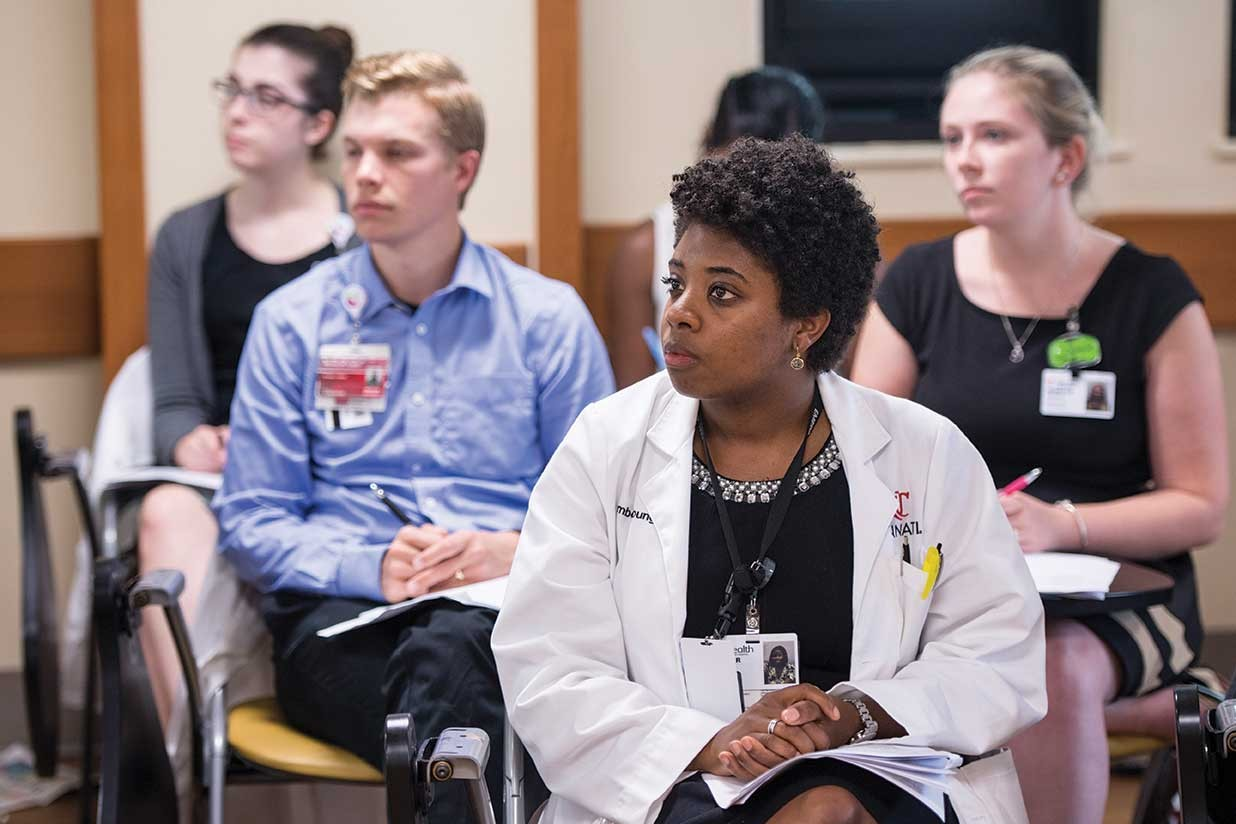 Several UC Medical residents sit in desks while listening to Bethany Yeiser speak.