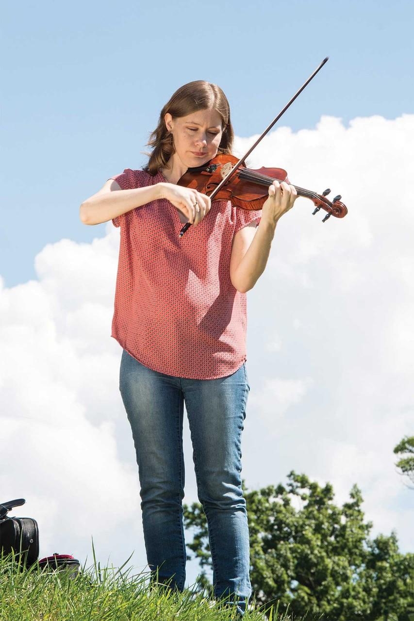Bethany Yeiser standing outside on campus playing violin