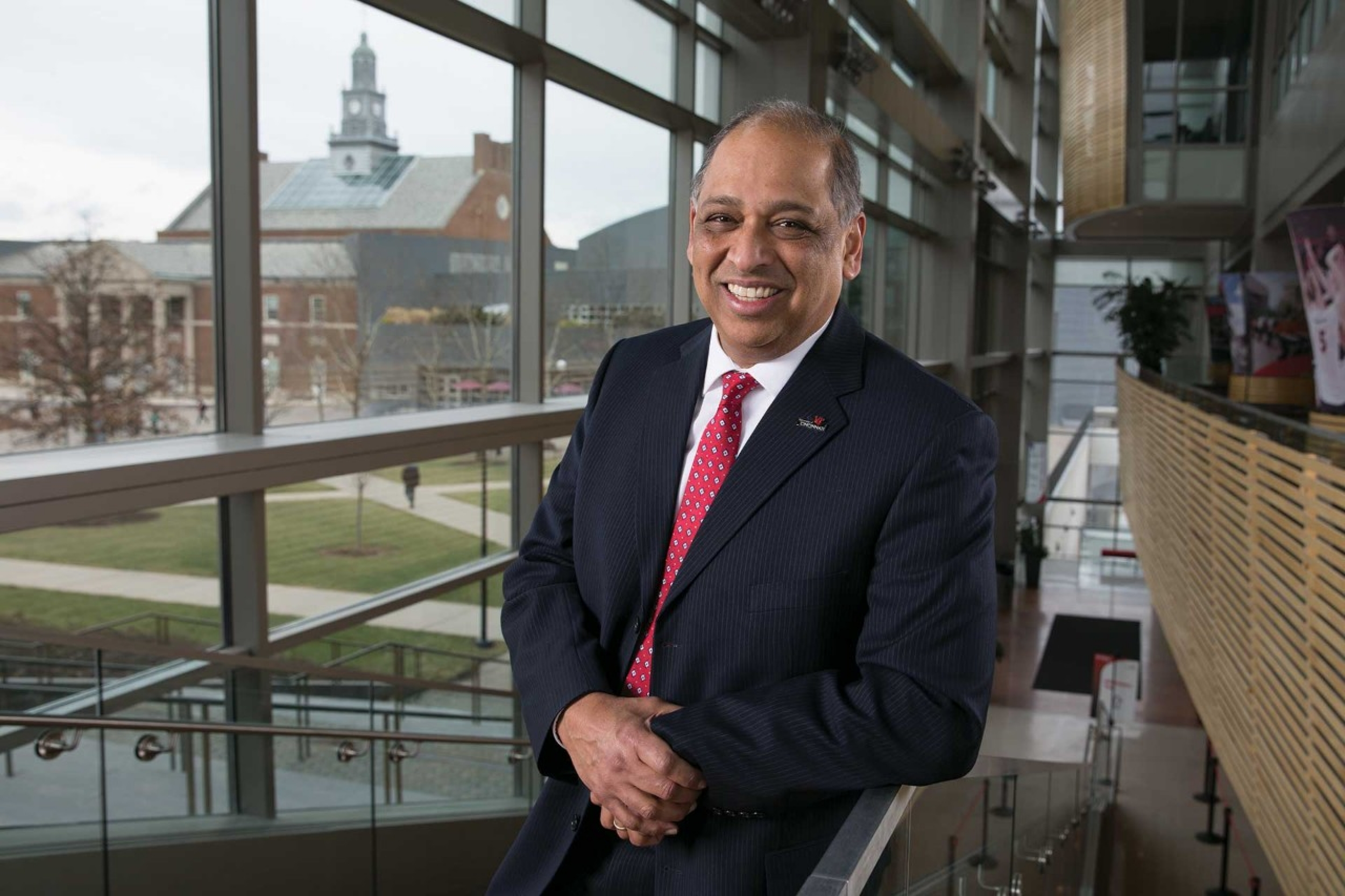 Portrait of President Pinto leaning on the staircase of University Pavilion with campus in the background.