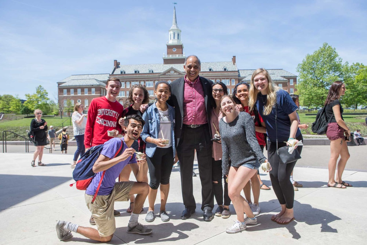 UC students and President Pinto with McMicken Hall in background.