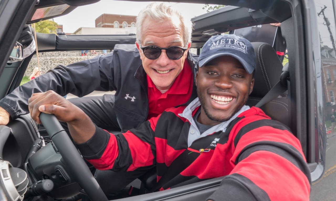 Peter Landgren poses with a UC student in a car during Homecoming