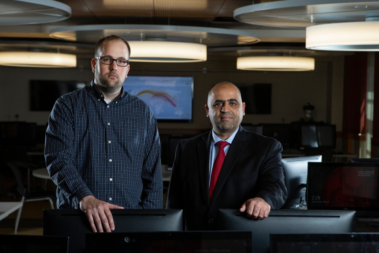 Jason Gerst and Hazem Said stand inside a lab in the School of Information Technology