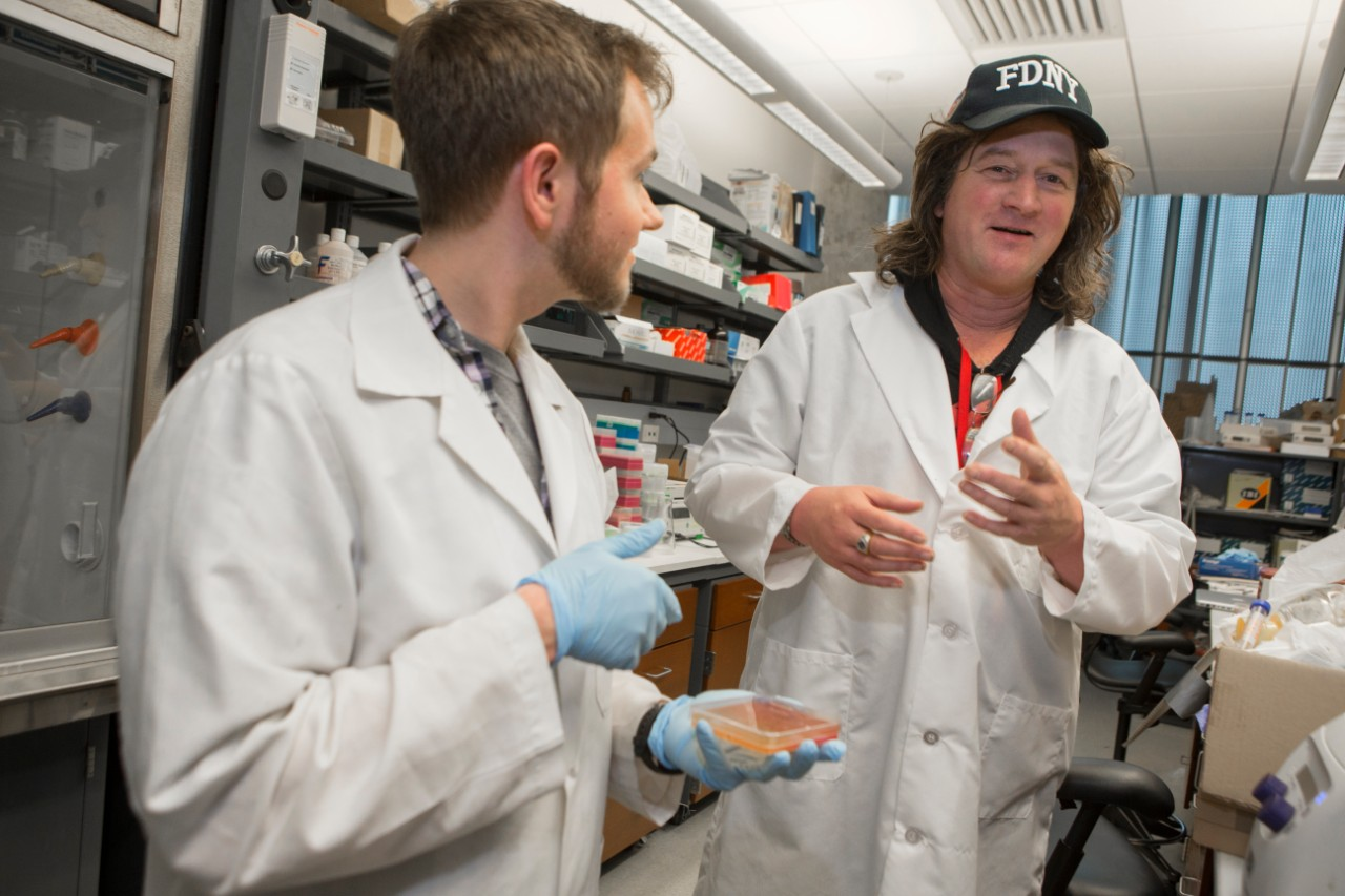 Former doctoral student Cameron McDaniel interacts with researcher Daniel Hassett in the lab.