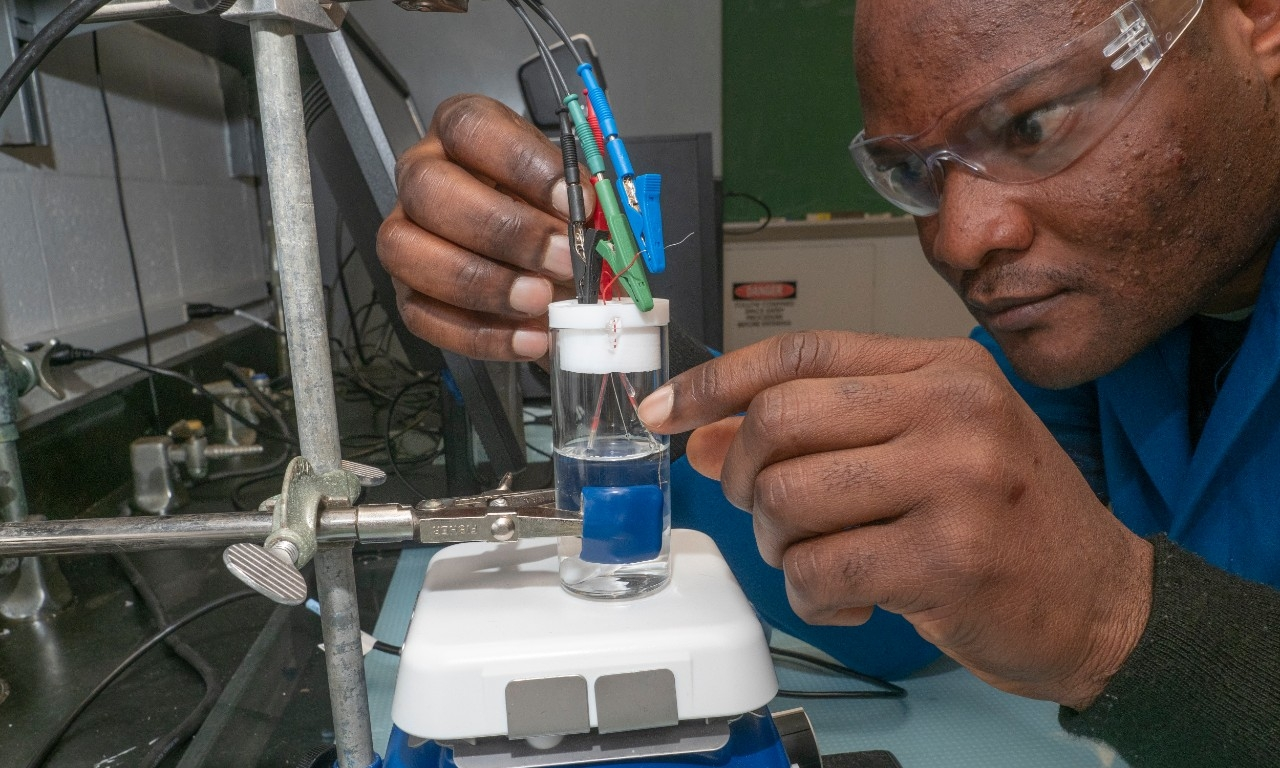 UC chemist Kolade Ojo manipulates a vial of water containing a carbon nanotube sensor attached to electric clamps.
