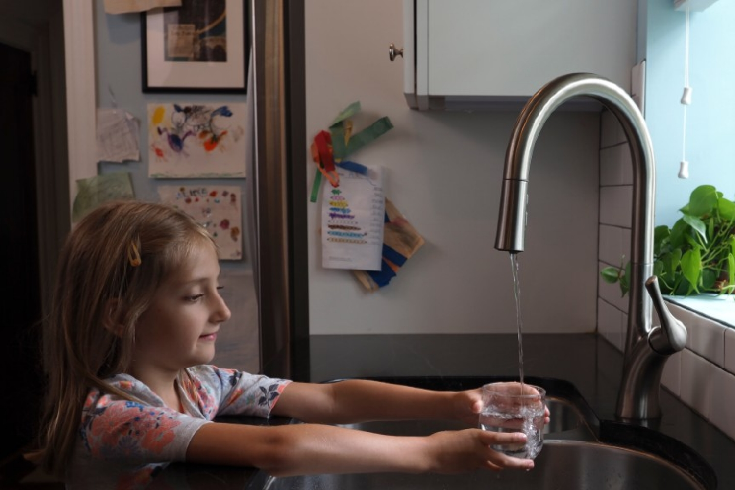 A young girl pours a glass of water from a tap
