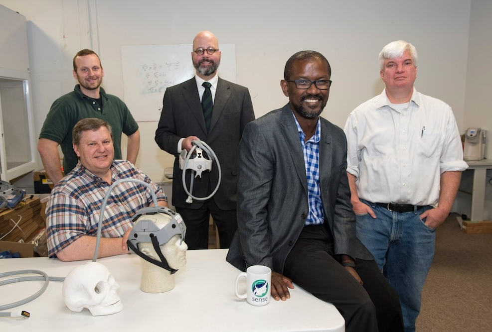 A group of researchers and doctors pose in a lab near a table with brain scan equipment