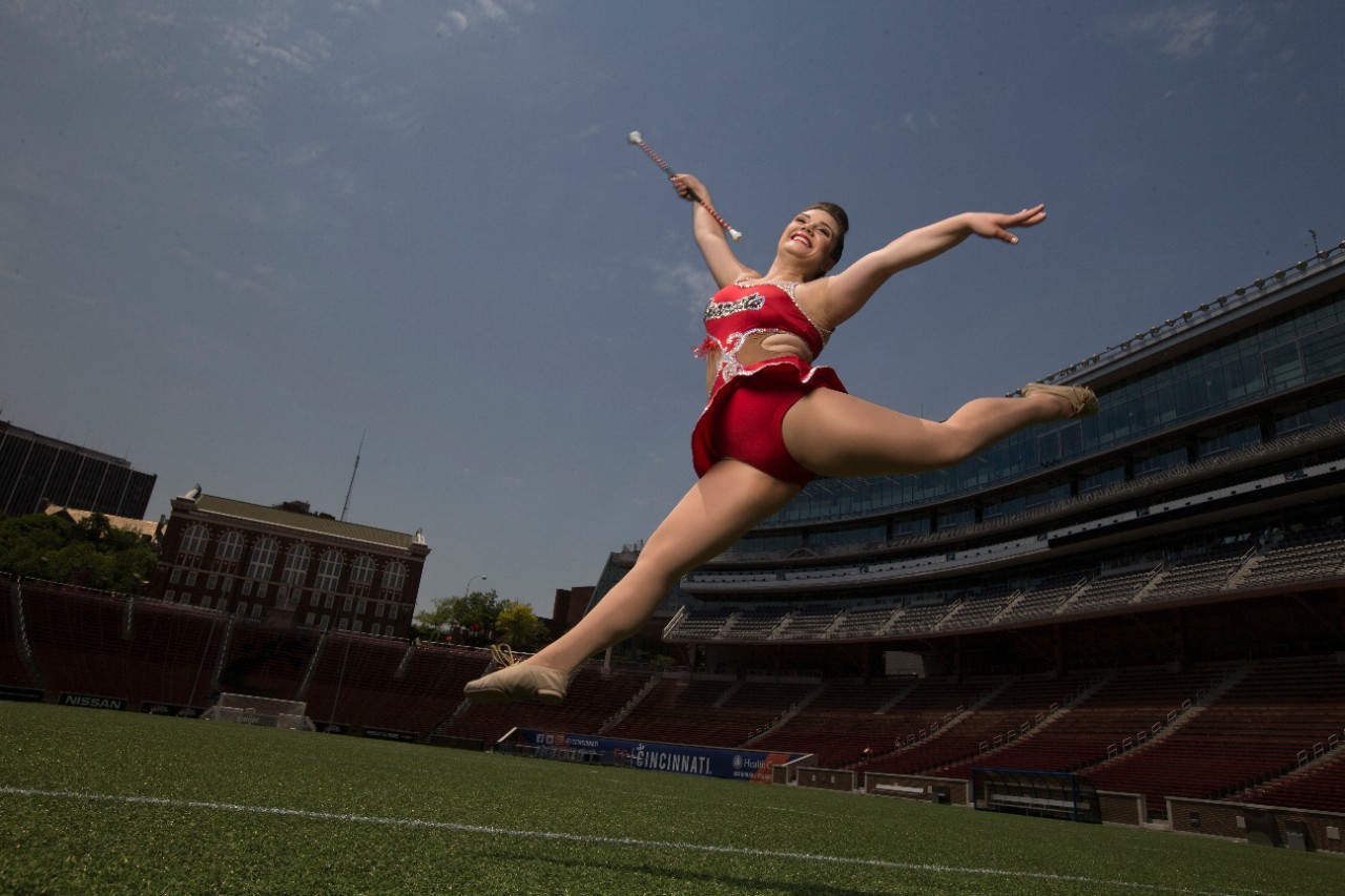 Woman in red sequin body suit twirls a baton on a football field